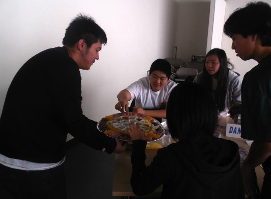Nathan Tadios serves manju from Fugetsu-Do Confectionery to Rising Stars members (from left) Derek Manaka, Dani Yang, Hiro Ozaki and Sharyse Watanabe.