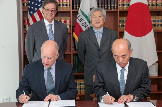 Gov. Jerry Brown and Japanese Ambassador to the U.S. Kenichiro Sasae sign a memorandum of cooperation. Behind them are California Environmental Protection Agency Secretary Matt Rodriquez and San Francisco-based Consul General of Japan Masato Watanabe. (Photo by Justin Short)