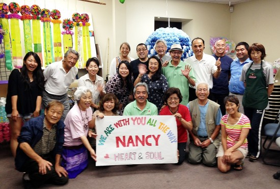 "Kikuchi's friends at the L.A. Tanabata Festival send a message of encouragement. The sign reads, ""We are with you all the way Nancy. Heart and Soul."" At the L.A. Tanabata Festival, which Kikuchi co-chaired, volunteers wore bright pink shirts in her honor."