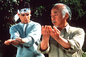 "Miyagi (Pat Morita) trains Daniel (Ralph Macchio) in a scene from ""The Karate Kid."""