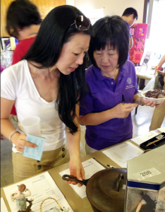WLA Bazaar Yang CAP: Kay Yang and her daughter Lauren display items for the silent auction. Among the items for sale will include jewelry created from broken pottery shards from Ishinomaki.