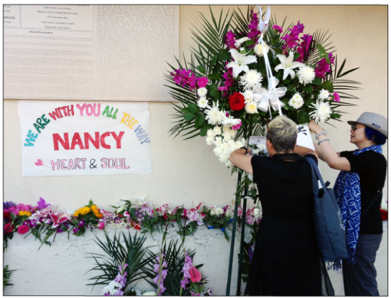 "Mourners place flowers on Saturday below the mural ""Home Is Little Tokyo"" in tribute to Nancy Kikuchi, who passed away on Sept. 10."
