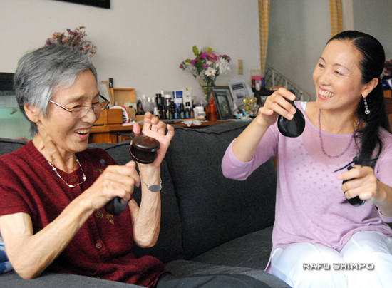 Katsuko Elegino, left, enjoys learning how to play castanets from her teacher, Michiyo Ando. (RYOKO NAKAMURA/Rafu Shimpo)
