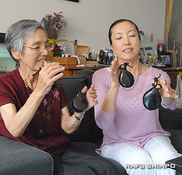 Michiyo Ando, right, teaches Katsuko Elegino, who is diagnosed with Alzheimer's disease, how to play castanets.