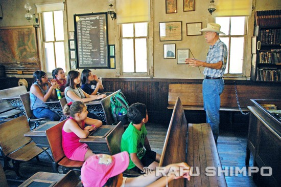 Knott's docent Steve Keesler gives young visitors a quick history lesson. The chart on the wall at the left lists many of the school's early teachers, along with their monthly salaries, ranging from 10 to 35 dollars.