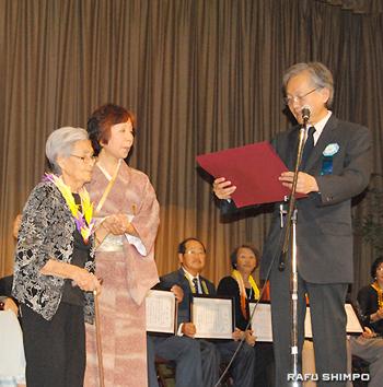 堀之内総領事から特別表彰状を贈られる100歳の吉岡さん(左)