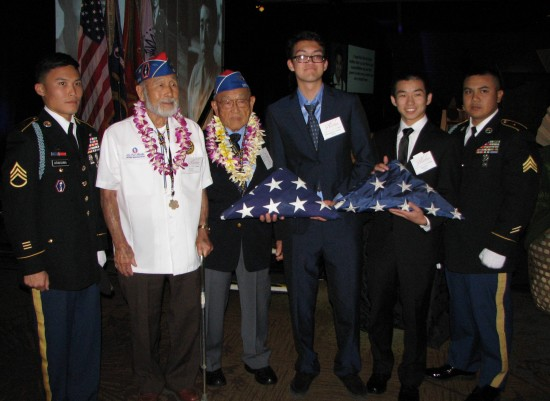 Taking part in an intergenerational flag ceremony during the Evening of Aloha gala were (from left): Sgt. Christopher Arakawa, 100th Battalion, 442nd Infantry Regiment Color Guard; 442nd Regimental Combat Team veterans Masao Takahashi and Tokuji Yoshihashi; high school grand prize winner Christopher Lindsay; college grand prize winner Spencer Tanaka; Sgt. Chris Makinano, 100th Battalion, 442nd Infantry Regiment Color Guard.  (J.K. YAMAMOTO/Rafu Shimpo)