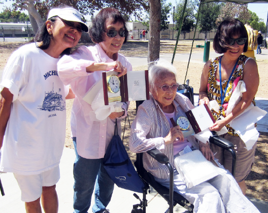 Chiyoko Ogawa (seated) is honored for turning 100 years old at the Nanka Shiga Club picnic. She is joined by (from left) Beverly Toyama, Nancy Kurihara-Johnson and Ann Gee.