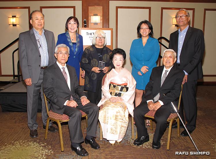 活動資金集めの晩餐会で行われた表彰式。前列左から受賞者の金井さん、藤間さん、前原さん。後列は中央が仲真所長、右隣がカタヤマ理事長