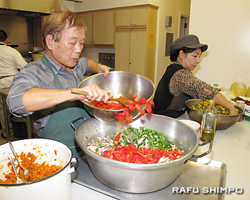 イベント用の料理を作る佐藤了(左)・芳江さん夫妻