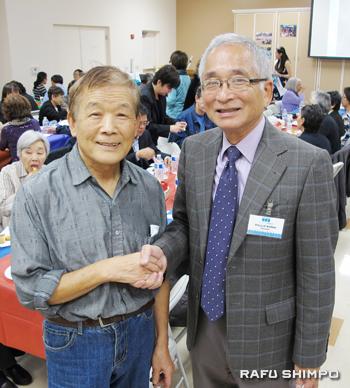 コマイ会長(右)と握手するアフリカ料理を提供した佐藤さん