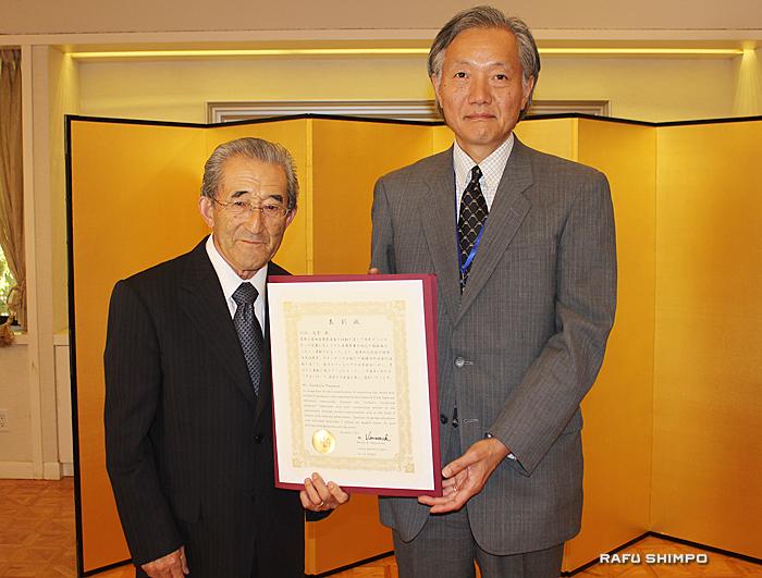 堀之内総領事(右)から表彰状を授与された小山さん