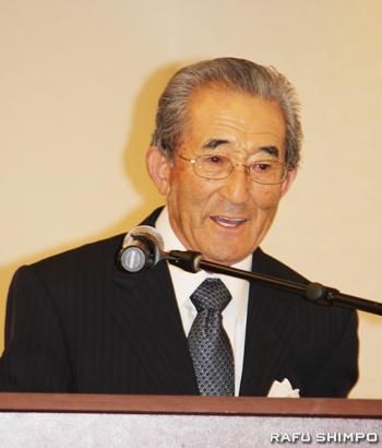 表彰式でこれまで支えてくれた妻そして日系社会に感謝の言葉を述べる小山さん