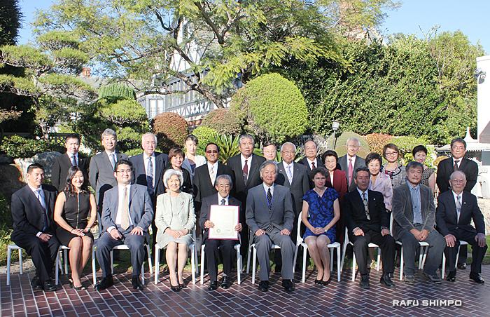 表彰式に臨席した家族や関係者と記念撮影に納まる小山さん(前列左から5人目)