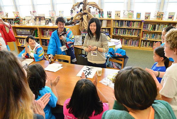 地元の中学校で開かれた日本文化の紹介イベント「ジャパン・デー」で、お手本を示し「礼文」と揮毫して、拍手をもらう研修生3人