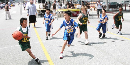 "Youthful basketball players from Little Tokyo and the broader Nikkei community participated in friendly competition at San-tai-San tournaments held on the streets of Little Tokyo in 2004. ""I like playing basketball because it's fun. I like the teamwork and the friends I make. We're all good friends,"" said one player."