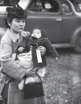 "This photo taken March 30, 1942 shows Fumiko Hayashida holding her daughter Natalie while being ""evacuated"" from Bainbridge Island, Wash. (Smithsonian Institution)"