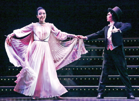 Chifumi (Grace Yoo) and Yuko (Jannelle Dote) perform in the style of Ginger Rogers and Fred Astaire in a lavish dance routine.
