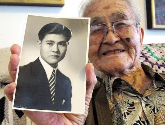 "Masao Yamashiro holds a photo of himself as a young man. Below, a copy of ""Tessaku,"" a literary journal published in Tule Lake. The journal kept to non-political topics but was still monitored by U.S. governmental authorities. (Photos by MARIO G. REYES/Rafu Shimpo)"