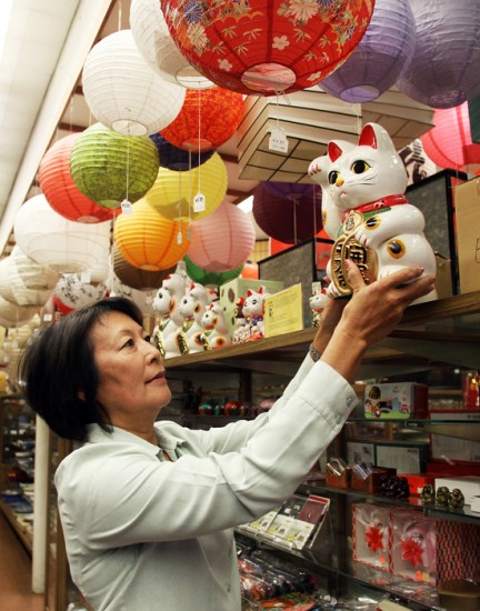 """Owner Irene Simonian arranges a maneki neko figure at Bunkado in Little Tokyo. The store was founded in 1945 by Tokio Ueyama as a """"house of culture"""" for artists. (Photos by MARIO G. REYES/Rafu Shimpo)"""