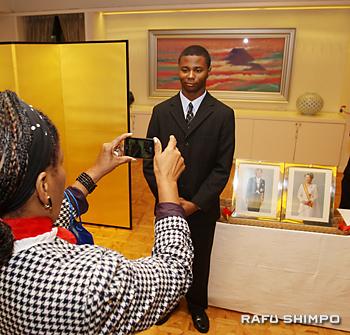 天皇皇后両陛下の写真の横に立ち、写真に納まるアンソニー・サントスさん