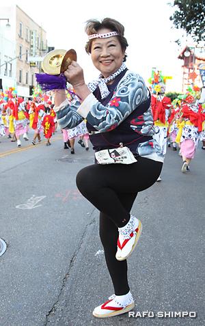パレードで鉦を鳴らす南加青森県人会の会長を務める奈良佳緒里さん
