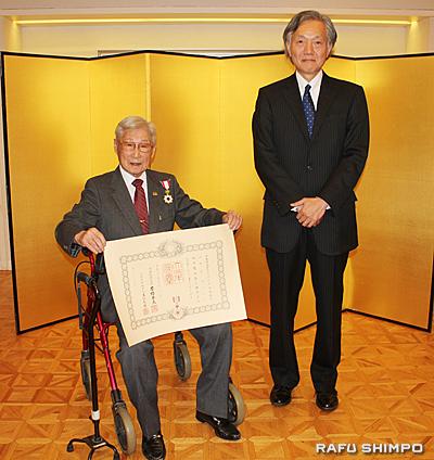伝達式で堀之内総領事(右)より勲章と賞状を授与された巽氏