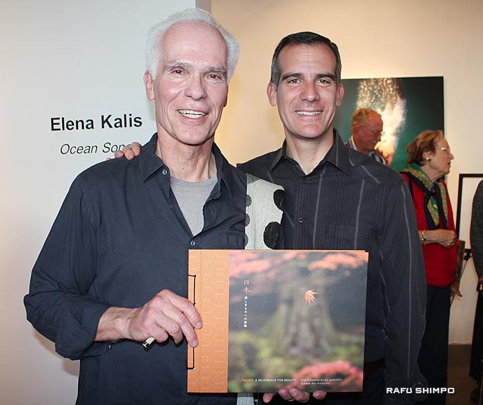 息子でLA市長のエリック・ガーセッティー氏(右)と写真に納まるギル・ガーセッティー氏。手に持っているのが、今回の写真集「日本、美しきものへの崇敬(Japan: A REVERENCE FOR BEAUTY)」