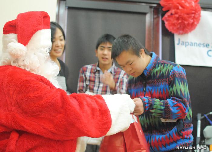 サンタクロースからプレゼントを手渡される佐藤友樹くん
