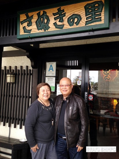 Junko and Hitoshi Komiyama pose in front of their restaurant in Gardena, Sanuki-no Sato. Hitoshi is a big fan of Bruce Willis and shaved his head as Willis did. They have been married for 41 years and have three boys. (RYOKO OHNISHI/Rafu Shimpo)