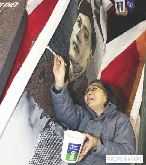 Janice Sadahiro decorates the float that pays tribute to Japanese American veterans of World War II. (MARIO G. REYES/Rafu Shimpo)