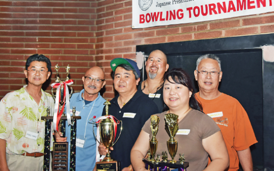 Kihei Otani (left), chairman of the Kenjinkai Kyogikai Bowling Tournament, and Richard Fukuhara, president of Nanka Yamaguchi Kenjinkai, pose with the tournament's high scoring team of Kevin Eto, Sam Nakata (back), Pei Eto and Russ Yamaguchi (back) of Yamaguchi Team C. Kevin Eto also won the trophy for Male High Series. Pei Eto captured Female High Series and Female High Game. (Photo by George Mori)