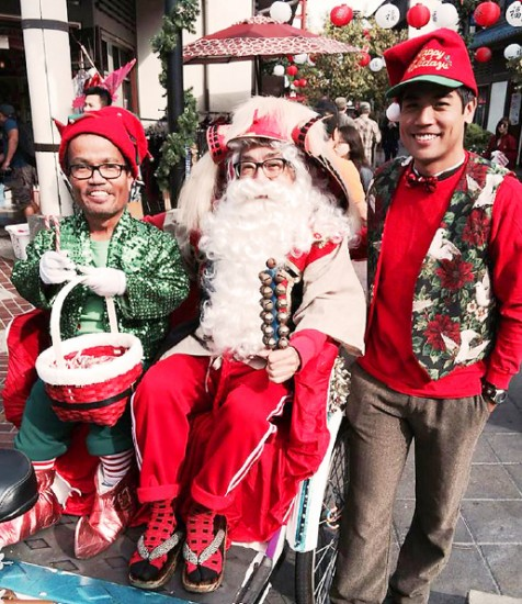 Elf John Tamaki, left, and Aaron Aoki accompanied Shogun Santa as he toured Little Tokyo on a bicycle-powered sleigh last Sunday. Santa will return to Weller Court Dec. 13, 14, 20, and 21, weather permitting.