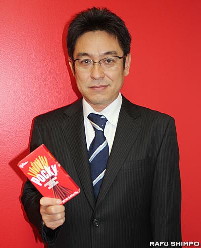 主力商品ポッキーを片手に米国での挑戦を語ってくれた米国江崎グリコ社の中井俊介社長