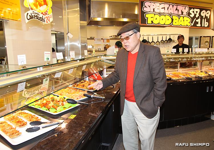 各種の総菜を見て回るヨシダソースの吉田潤喜代表取締会長