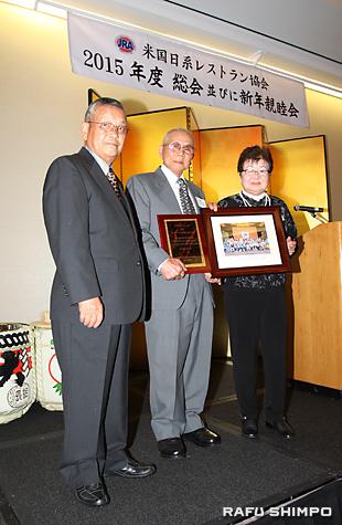 キクチさんの表彰式。波多野会長(左)から、代理で賞状を受け取るナンシーさんの両親の菊池安雄・メイ夫妻