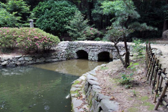 Megane-bashi or Eyeglass Bridge over a koi pond at Ooasa-hiko Shrine garden. (ICHIRO SHIMIZU/Rafu Shimpo)