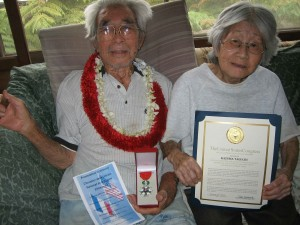 Kazuma Taguchi, pictured with his wife Yasuko, was unable to attend and received his medal at home.