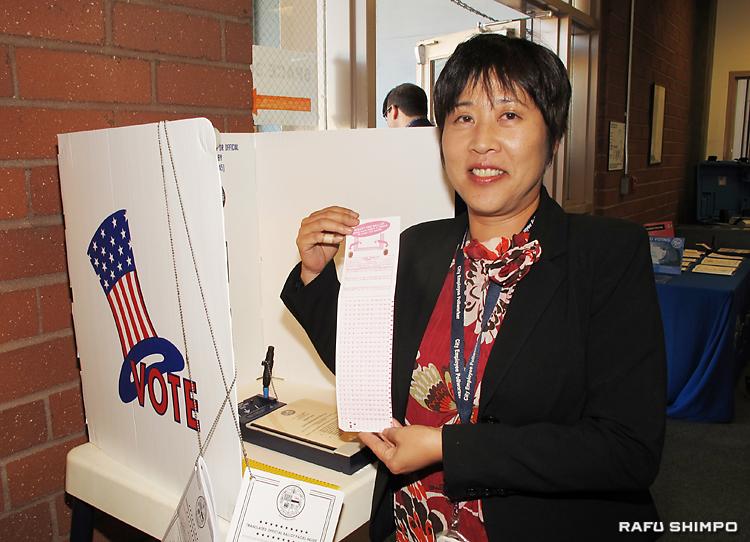 投票用紙のサンプルを披露する日本語担当スタッフの山本由佳さん