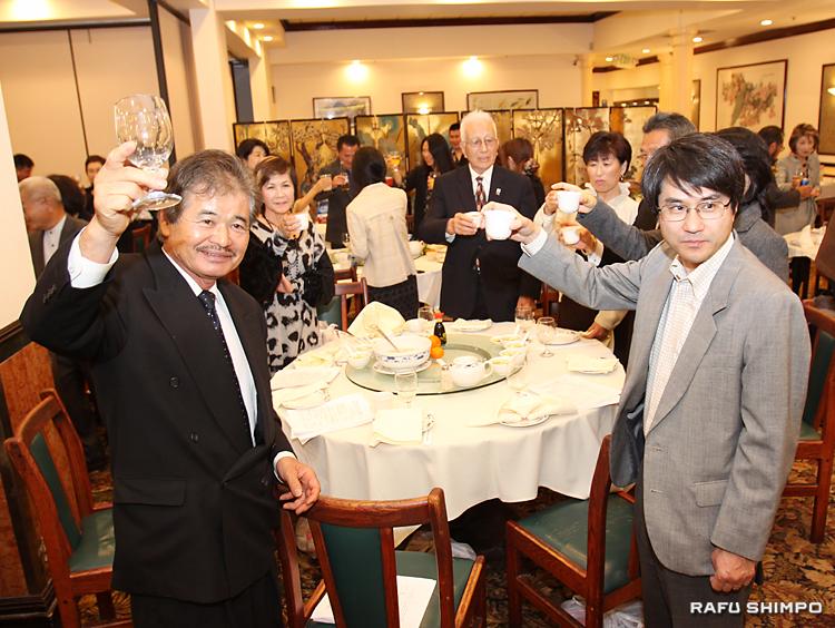 新年の乾杯をする小田新会長(左)。右は新村領事