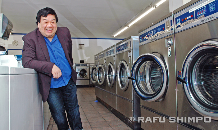 "Peter Kuo laughs amongst the suds and spin cycles in South Pasadena on Tuesday. He is directing the latest from East West Players, the comedy ""Washer/Dryer."" (MIKEY HIRANO CULROSS/Rafu Shimpo)"