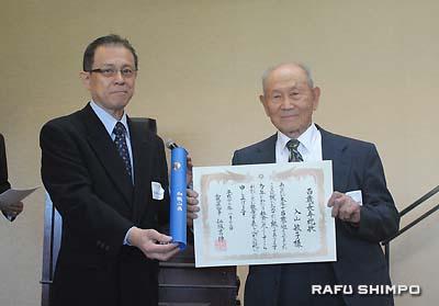 県庁から100歳の表彰を受けた入山敏子さんに代わり、代理で賞状を受け取った入山正夫さん(右)と有地会長