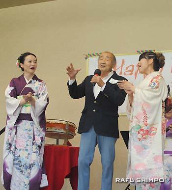 松豊会のメンバーと和歌山県の民謡「串本節」を歌う会員のチャーリー・浜崎さん(中央)