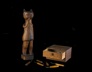 A hand-carved wooden ashtray in the shape of a cat.