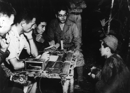 SIMINI, New Guinea, January 2, 1943: From left, Major Hawkins, Phil Ishio and Arthur Ushiro Castle of the 32nd Infantry Division question a prisoner taken in the Buna campaign. Information from POW interrogations produced vital tactical information countless times. National Archives photo
