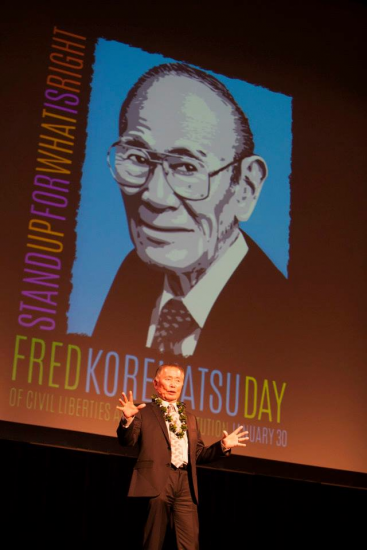 George Takei speaks with an image of the late Fred Korematsu projected behind him.