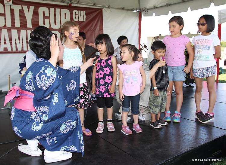 ステージに上がって民謡を元気よく唄う子供たち