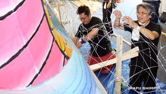 Takenami Hiroo (right), a nebuta master, works on the float.