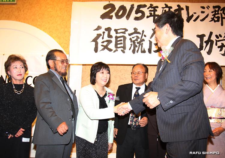 就任式に立ち会ったナカムラ氏(手前)から激励を受ける新役員。左から3人目が藤田喜美子会長