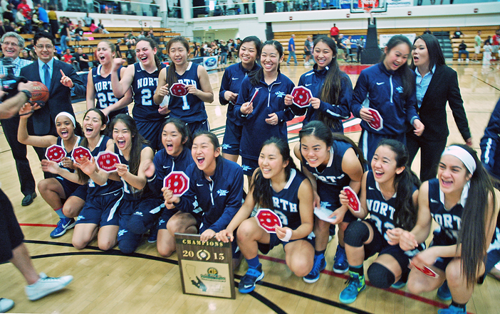 Oblivious to head coach Lauren Kamiyama (right) trying to shoo them off the court, the members of the North Torrance High School girls' basketball team continue to celebrate their CIF-SS Div. 3AA championship, Saturday at Azusa Pacific University. (Photos by MIKEY HIRANO CULROSS/Rafu Shimpo)